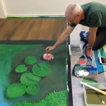 Matt Ottley painting a mural at Heidi's Place bookstore in Murwillumbah