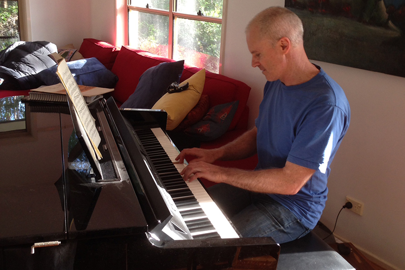 Matt Ottley composing music on Yamaha piano